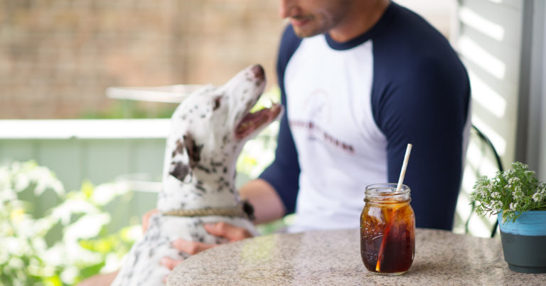 man pets dalmation on patio with cool drink