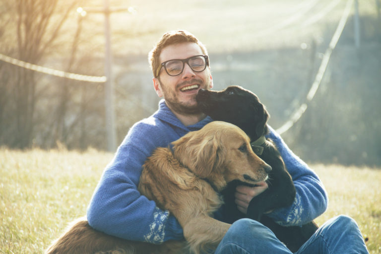 man cuddling two dogs outdoors