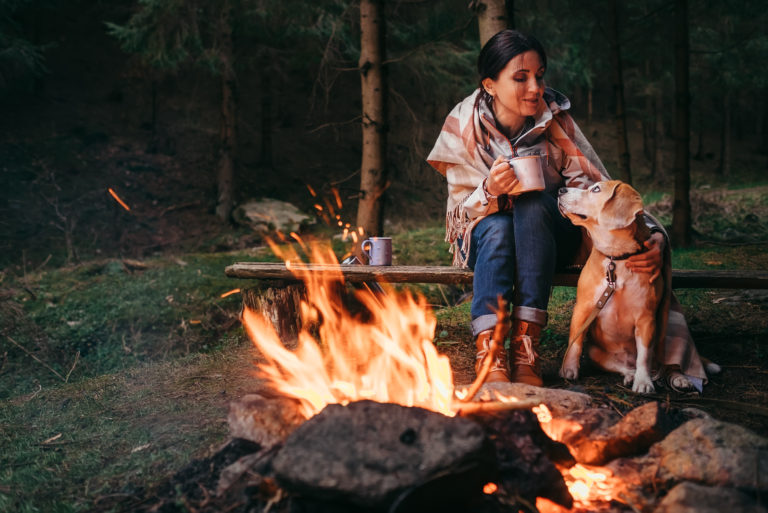 woman sits next to campfire with her dog and coffee