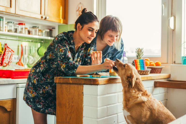 two women feed dog at kitchen counter, pride