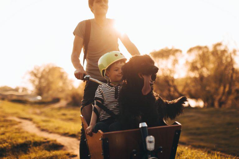 Man takes son and dog for ride in bike basket